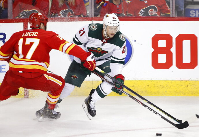 Minnesota Wild defenseman Carson Soucy (21) has the puck knocked off his stick by Calgary Flames left wing Milan Lucic (17) during the second period of an NHL hockey game Thursday, Jan. 9, 2020, in Calgary, Alberta. (Larry MacDougal/The Canadian Press via AP)