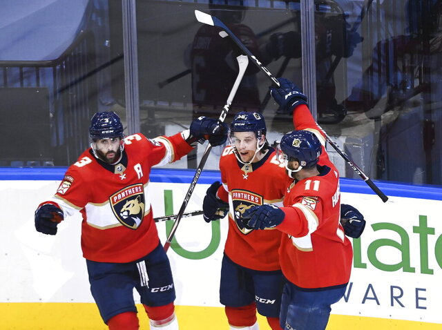 Florida Panthers left wing Erik Haula (56) celebrates his goal with teammates Keith Yandle (3) Jonathan Huberdeau (11) after scoring against the New York Islanders during the second period of an NHL Stanley Cup playoff hockey game in Toronto, Ontario, Wednesday, Aug. 5, 2020. (Nathan Denette/The Canadian Press via AP)