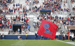 In this Sept. 8, 2018, photo, a Mississippi cheerleader waves the school flag in front of a number of empty end zone seats during their home opener against Southern Illinois, in Oxford, Miss. The SEC saw a drop of more than 2,400 fans per game last season, which was the biggest decline of any Power Five conference. (AP Photo/Rogelio V. Solis)