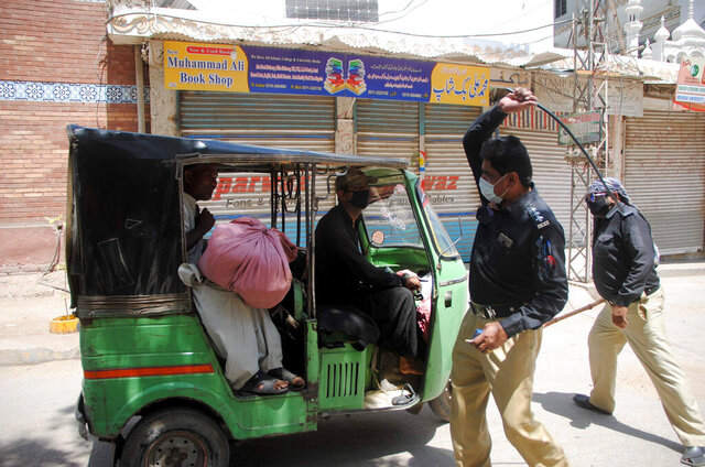 Police officers restrict a rickshaw driver defying the nation-wide lockdown to curb the spread of the coronavirus in Hyderabad, Pakistan, Friday, March, 3, 2020. (Some mosques were allowed to remain open in Pakistan on Friday, the Muslim sabbath when adherents gather for weekly prayers, even as the coronavirus pandemic spread and much of the country had shut down. (AP Photo/Pervez Masih)