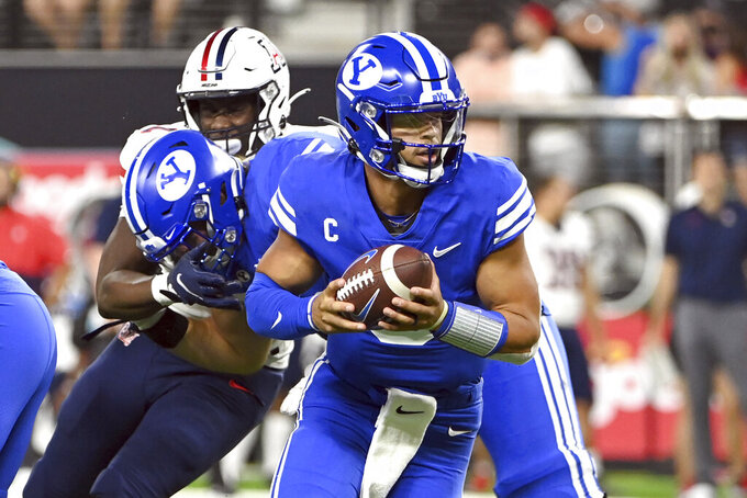 BYU quarterback Jaren Hall looks to hand off the ball against Arizona during the second half of an NCAA college football game Saturday, Sept. 4, 2021, in Las Vegas. (AP Photo/David Becker)