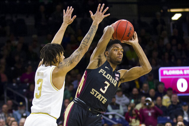 Florida State's Trent Forrest, left, passes the ball away from Notre Dame's Prentiss Hubb during the first half of an NCAA college basketball game Wednesday, March 4, 2020, in South Bend, Ind. (AP Photo/Robert Franklin)