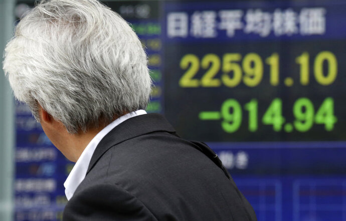 A man looks at an electronic stock board of a securities firm in Tokyo, Thursday, Oct. 11, 2018. Asian markets tumbled on Thursday, after Wall Street slumped on a heavy selling of technology and internet stocks. Japan's benchmark fell by an unusually wide margin of 3.9 percent. (AP Photo/Koji Sasahara)