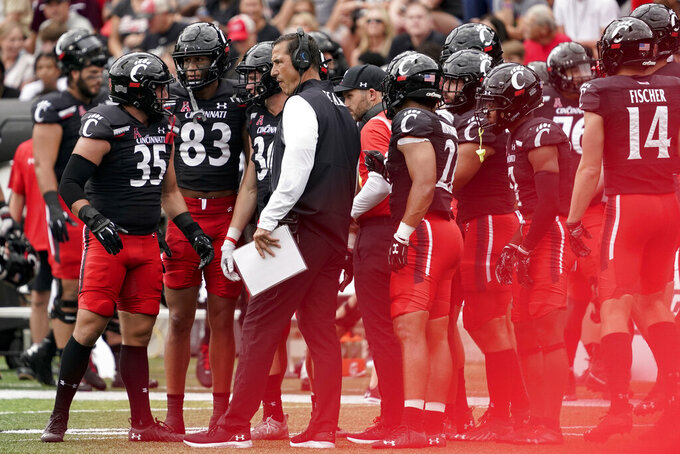 Cincinnati head coach Luke Fickell speaks with his team on the sideline during the first half of an NCAA college football game against Miami (Ohio), Saturday, Sept. 4, 2021, in Cincinnati. (AP Photo/Jeff Dean)