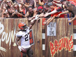 Cleveland Browns running Kareem Hunt high-fives fans in the dawg pound after a touchdown during an Orange and Brown NFL football practice in Cleveland, Sunday, Aug. 8, 2021. (John Kuntz/The Plain Dealer via AP)