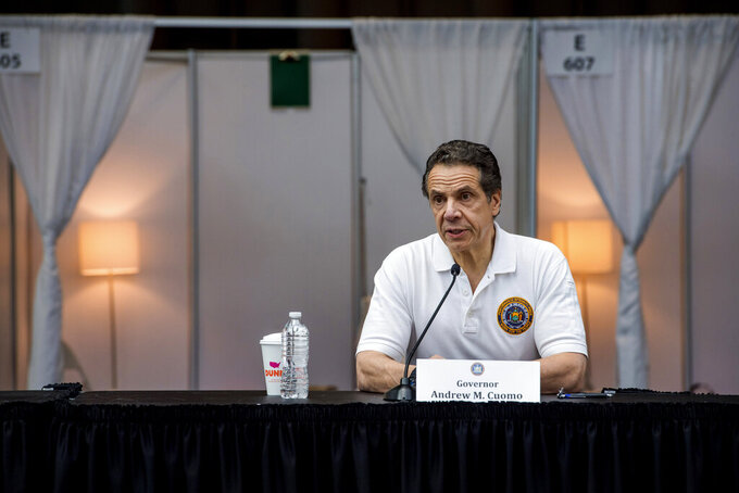 In this Friday, March 27, 2020 photo provided by Office of Governor Andrew M. Cuomo Gov. Andrew Cuomo, briefs the media inside a nearly completed makeshift hospital at the Jacob Javits Convention Center in New York. Cuomo said the state wants to build four more temporary hospitals in New York City within weeks, before coronavirus cases are projected to peak. (Darren McGee/Office of Governor Andrew M. Cuomo via AP)