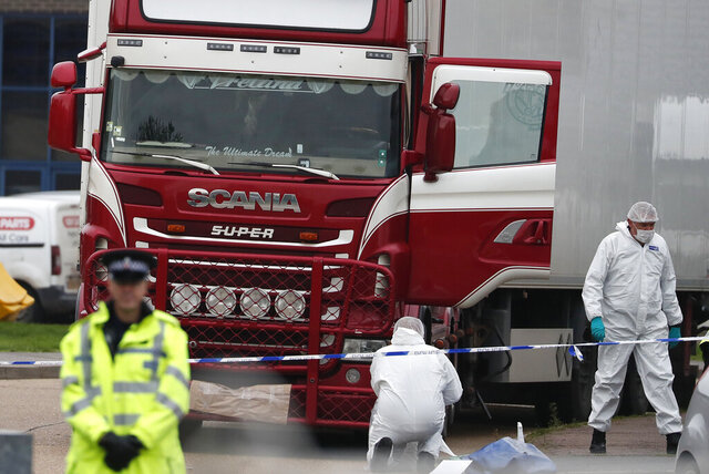 FILE - In this file photo dated Wednesday Oct. 23, 2019, Police forensic officers attend the scene after a truck was found to contain a large number of dead bodies, in Grays, South England.  Police said Tuesday Feb. 11, 2020, that a provisional postmortem examination of 39 bodies found inside this shipping container in England concluded that the victims from Vietnam died of a combination of insufficient oxygen and overheating in a closed space.  Police said Feb. 11, they are continuing to make progress in a complex investigation. (AP Photo/Alastair Grant, FILE)