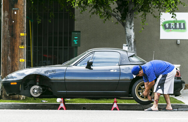FILE - In this Sept. 10, 2015, file photo, a man repairs one of the two tires that he said blew up suddenly while driving on Interstate 5 in Los Angeles. Tires are of vital importance since they are the only part of the vehicle that makes contact with the road. Yet motorists often neglect their condition and age, and the results can be catastrophic. In its most recently available information, the National Highway Traffic Safety Administration says that 738 people died in 2017 from tire-related crashes. (AP Photo/Damian Dovarganes, File)