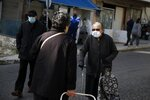 An elderly woman wearing a face mask against the spread of coronavirus, speaks with another woman, in Athens, Monday, Nov. 23, 2020. Greece has seen a major resurgence of the virus after the summer, leading to dozens of deaths each day and thousands of new infections. (AP Photo/Thanassis Stavrakis)