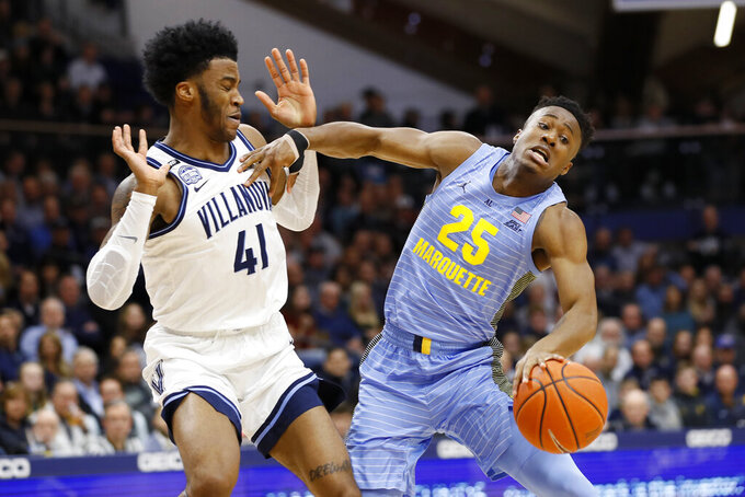 Marquette's Koby McEwen (25) tries to dribble past Villanova's Saddiq Bey (41) during the first half of an NCAA college basketball game Wednesday, Feb. 12, 2020, in Villanova, Pa. (AP Photo/Matt Slocum)