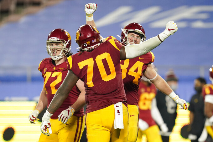Southern California offensive lineman Andrew Vorhees (72), offensive lineman Jalen McKenzie (70) and tight end Erik Krommenhoek (84) celebrate a touchdown during the fourth quarter of an NCAA college football game against UCLA, Saturday, Dec 12, 2020, in Pasadena, Calif. (AP Photo/Ashley Landis)