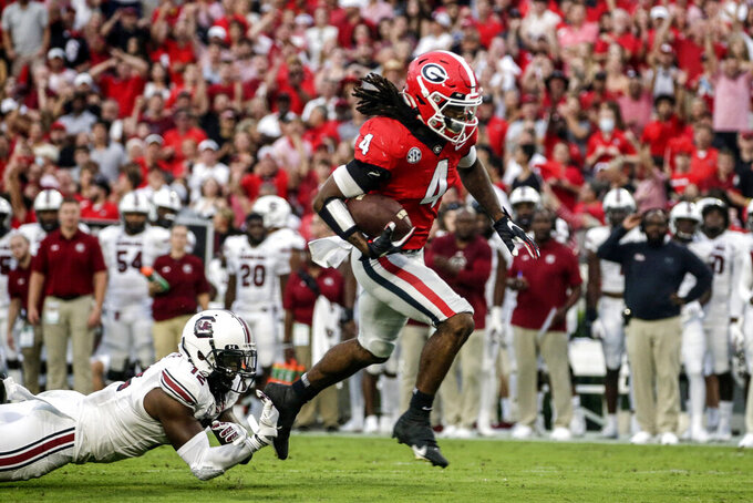 Georgia running back James Cook (4) breaks free from the tackle attempt by South Carolina defensive back Jaylan Foster (12) on the way to a touchdown during the first half of an NCAA college football game Saturday, Sept. 18, 2021, in Athens, Ga. (AP Photo/Butch Dill)