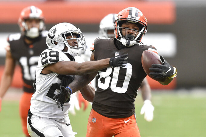 FILE - In this Sunday, Nov. 1, 2020 file photo, Cleveland Browns wide receiver Jarvis Landry (80) makes a one-handed catch beside Las Vegas Raiders free safety Lamarcus Joyner (29) during an NFL football game in Cleveland. Every day on the practice field, Jarvis Landry looks around and expects to see Odell Beckham Jr. dancing during warmups or running pass routes alongside him. But his best friend and teammate isn't around _ and won't be until next year. (AP Photo/David Richard, File)
