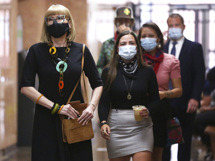 Teacher Sheila Buck, left, Norman City Councilor Alexandra Scott and Ashley McCray arrive for their arraignment at the Tulsa County Courthouse in Tulsa, Okla., Thursday, Aug. 6, 2020. Buck and three other people arrested at a Tulsa campaign rally for President Donald Trump, pleaded not guilty Thursday to misdemeanor obstruction charges. (Mike Simons/Tulsa World via AP)