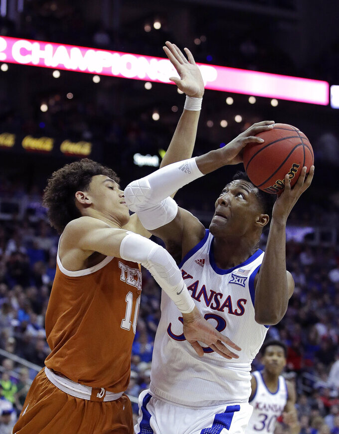 Kansas' David McCormack (33) looks to shoot under pressure from Texas' Jaxson Hayes during the first half of an NCAA college basketball game in the Big 12 men's tournament Thursday, March 14, 2019, in Kansas City, Mo. (AP Photo/Charlie Riedel)
