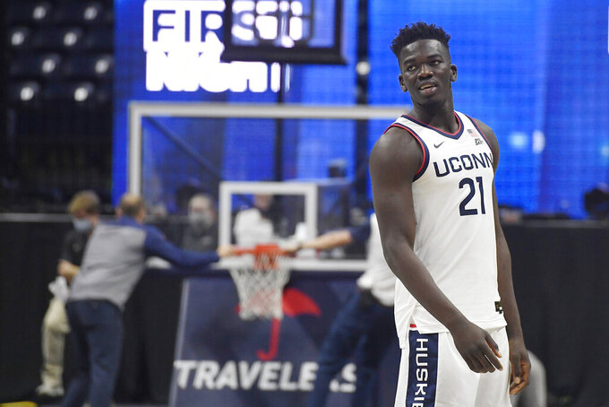 Connecticut's Adama Sanogo watches First Night events for the UConn men's and women's NCAA college basketball teams as people work on a stuck basketball hoop behind him, Friday, Oct. 15, 2021, in Storrs, Conn. (AP Photo/Jessica Hill)