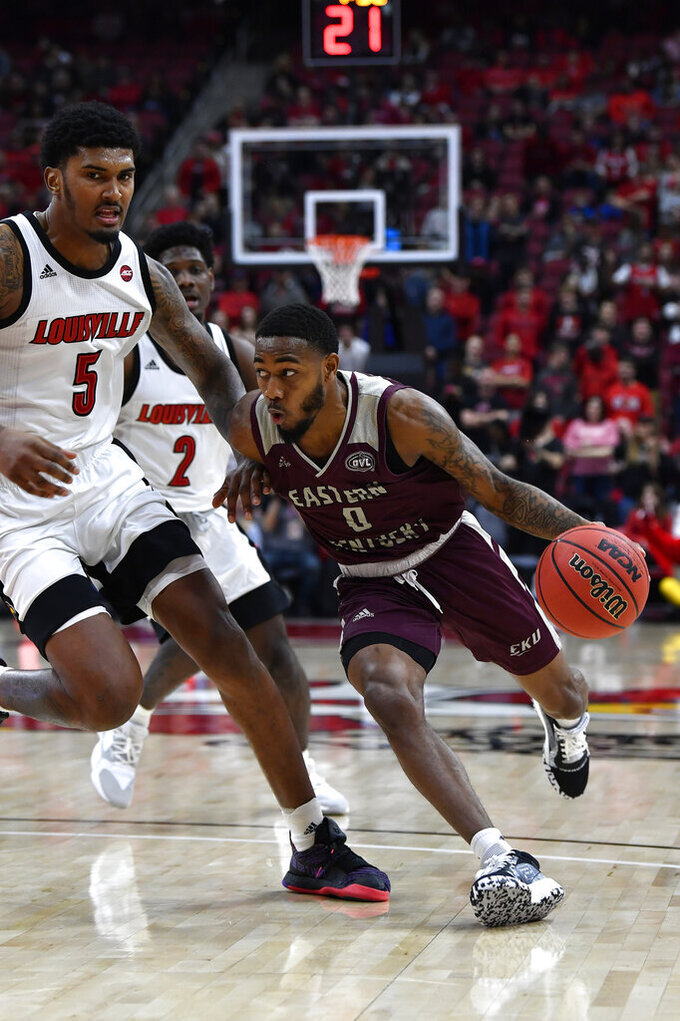 Eastern Kentucky guard Russhard Cruickshank (0) tries to drive past the defense of Louisville forward Malik Williams (5) during the first half of an NCAA college basketball game in Louisville, Ky., Saturday, Dec. 14, 2019. (AP Photo/Timothy D. Easley)