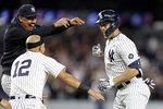 New York Yankees' Giancarlo Stanton, right, is congratulated by Nestor Cortes Jr. and Rougned Odor (12) after hitting a walkoff single during the 11th inning of a baseball game against the Baltimore Orioles, Friday, Sept. 3, 2021, in New York. (AP Photo/Adam Hunger)