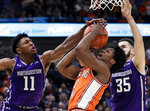 Illinois guard Andres Feliz, center, shoots against Northwestern guard Anthony Gaines, left, and forward Aaron Falzon during the second half of an NCAA college basketball game in the first round of the Big Ten Conference tournament in Chicago, Wednesday, March 13, 2019. Illinois won 74-69 in overtime. (AP Photo/Nam Y. Huh)