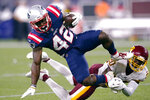 New England Patriots running back J.J. Taylor (42) tries to get away from Washington Football Team cornerback Jimmy Moreland (20) during the first half of a preseason NFL football game Thursday, Aug. 12, 2021, in Foxborough, Mass. (AP Photo/Elise Amendola)