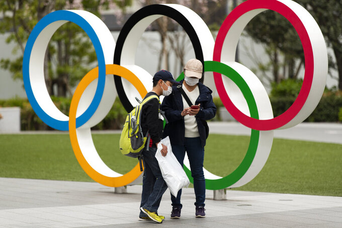 """A boy looks at a cellphone after his mother took pictures of him in front of a display of the Olympic rings at the Japan Olympic Museum in Tokyo on Friday, April 2, 2021. Tokyo pitched itself as """"a safe pair of hands"""" when it was awarded the Olympics 7 1/2 years ago. Now, nothing is certain as Tokyo's postponed Olympics hit the 100-days-to-go mark on Wednesday, April 14, 2021. (AP Photo/Hiro Komae)"""
