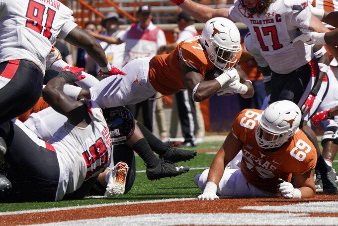 Texas running back Keilan Robinson (7) dives for a touchdown against Texas Tech during the second half of an NCAA college football game on Saturday, Sept. 25, 2021, in Austin, Texas. (AP Photo/Chuck Burton)