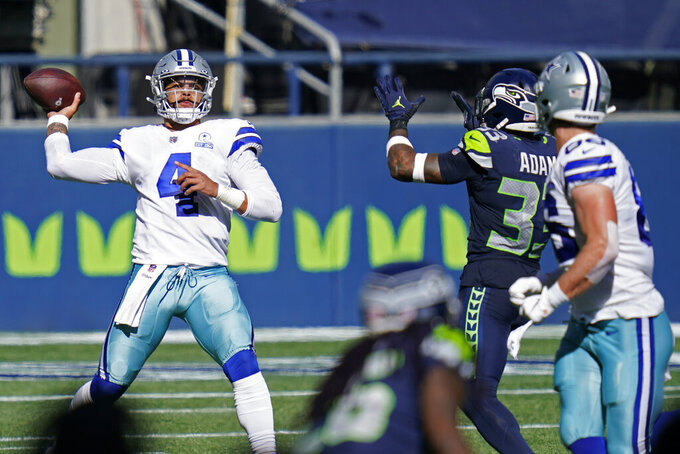Dallas Cowboys quarterback Dak Prescott (4) passes under pressure from Seattle Seahawks strong safety Jamal Adams, second from right, during the first half of an NFL football game, Sunday, Sept. 27, 2020, in Seattle. (AP Photo/Elaine Thompson)