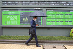 A man walks by an electronic stock board of a securities firm in Tokyo, Wednesday, April 14, 2021. Asian stock markets rose Wednesday after Wall Street hit a high following an uptick in U.S. inflation and an order by regulators to suspend use of Johnson & Johnson's coronavirus vaccine. (AP Photo/Koji Sasahara)