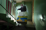 FILE - In this Thursday, April 30, 2020 file photo, Galina Yakovleva pulls a cart with a charity food and goods to a woman in need in St.Petersburg, Russia. Every day amid the coronavirus pandemic, the 80-year-old Leningrad siege survivor Galina Yakovleva has driven to the city in her minivan to bring charity groceries and goods to elderly people and families with children in need. (AP Photo/Dmitri Lovetsky)