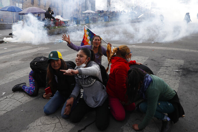 In this Friday, Nov. 15, 2019 photo, supporter of former President Evo Morales protect themselves from tear gas launched by the police, in La Paz, Bolivia. Bolivia's new interim president Jeanine Anez faces the challenge of stabilizing the nation and organizing national elections within three months at a time of political disputes that pushed Morales to fly off to self-exile in Mexico after 14 years in power. (AP Photo/Natacha Pisarenko)