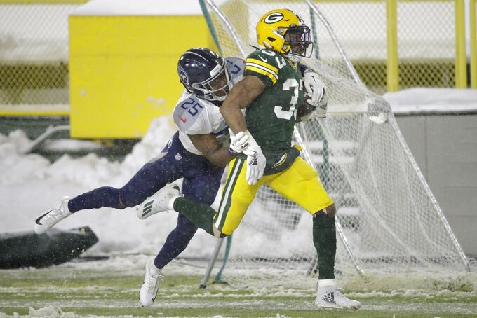 Green Bay Packers' Aaron Jones is stopped by Tennessee Titans' Adoree' Jackson during the second half of an NFL football game Sunday, Dec. 27, 2020, in Green Bay, Wis. (AP Photo/Mike Roemer)