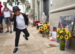 Dominic Lendo dances in front of Michael Jackson's mausoleum at Forest Lawn Cemetery in Glendale, Calif., on Tuesday, June 25, 2019, on the 10th Anniversary of Jackson's death. Fans are gathering to pay tribute to the King of Pop, congregating at his former home, the cemetery where he is interred and his star on the Hollywood Walk of Fame. His estate is calling on the superstar's fans to perform acts of service in Jackson's memory. (AP Photo/Richard Vogel)