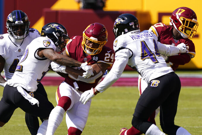 Washington Football Team running back Antonio Gibson (24) runs into Baltimore Ravens cornerback Marlon Humphrey (44) during the first half of an NFL football game, Sunday, Oct. 4, 2020, in Landover, Md. (AP Photo/Susan Walsh)