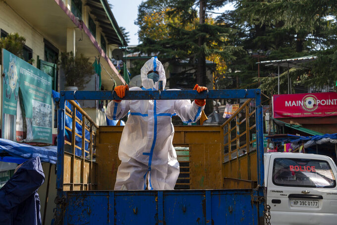 A government health worker in protective suit waits to sanitise a street shut down to prevent the spread of the coronavirus in Dharmsala, India, Thursday, Dec. 10, 2020. (AP Photo/Ashwini Bhatia)