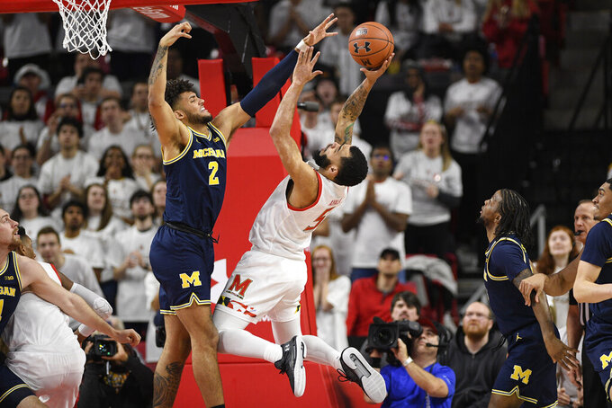 Maryland guard Eric Ayala (5) goes to the basket next to Michigan forward Isaiah Livers (2) during the first half of an NCAA college basketball game, Sunday, March 8, 2020, in College Park, Md. (AP Photo/Nick Wass)