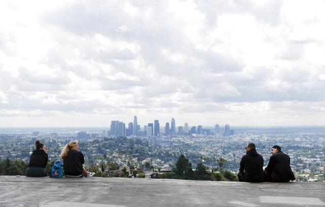 Two pairs of hikers maintain distance as they mingle at Vista View Point in Griffith Park, Friday, March 20, 2020, in Los Angeles. California Gov. Gavin Newsom issued a statewide stay-at-home order Thursday for residents to venture outside only for essential jobs, errands and some exercise, due to coronavirus concerns. (AP Photo/Chris Pizzello)