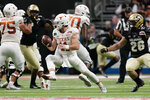 Texas quarterback Sam Ehlinger (11) sidesteps Colorado linebacker Carson Wells (26) during the first half of the Alamo Bowl NCAA college football game Tuesday, Dec. 29, 2020, in San Antonio. (AP Photo/Eric Gay)