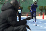 In this Feb. 12, 2020, photo, Joseph Akoon Akoon, of the South Sudan team practices as coach Joseph Omirok, marks time of runs during their training ifor the Tokyo 2020 Olympics and Paralympics in Maebashi, Gunma Prefecture, north of Tokyo. (AP Photo/Eugene Hoshiko)