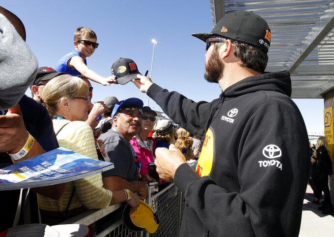 A young fan receives an autograph from driver Martin Truex Jr. prior to the start of the NASCAR Cup Series auto race at ISM Raceway, Sunday, March 10, 2019, in Avondale, Ariz. (AP Photo/Ralph Freso)