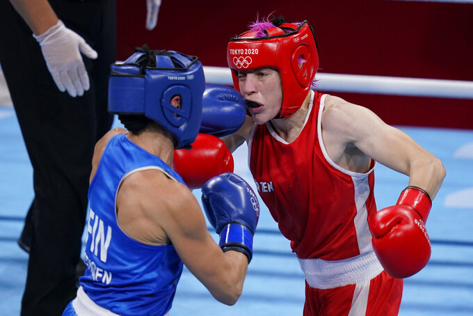 France's Maiva Hamadouche, right, exchanges punches with Finland's Mira Majut Johanna Potkonen during their women's lightweight 60-kg boxing match at the 2020 Summer Olympics, Tuesday, July 27, 2021, in Tokyo, Japan. (AP Photo/Frank Franklin II)