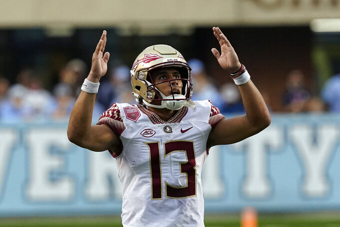 Florida State quarterback Jordan Travis (13) signals for a touchdown during the second half of an NCAA college football game against North Carolina in Chapel Hill, N.C., Saturday, Oct. 9, 2021. (AP Photo/Gerry Broome)