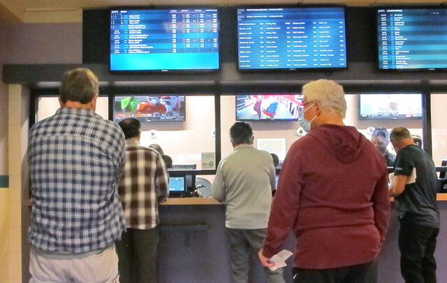 Customers line up to make sports bets at Freehold Raceway in Freehold, N.J. on Oct. 24, 2020. New Jersey lawmakers want to amend the state constitution to allow sports betting on all major collegiate games, removing a big restriction in a wagering market that is smashing national sports betting records. A bill calling for a public referendum in 2021 was amended Monday, Nov. 9, 2020 to significantly expand collegiate sports betting in the state. (AP Photo/Wayne Parry)