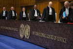 Presiding judge Abdulqawi Ahmed Yusuf, center, and other judges take their seats at the International Court in The Hague, Netherlands, Thursday, Jan. 23, 2020. The United Nations' top court is scheduled to issue a decision on a request by Gambia to order Myanmar to halt what has been cast as a genocidal campaign against the southeast Asian country's Rohingya Muslim minority. (AP Photo/Peter Dejong)