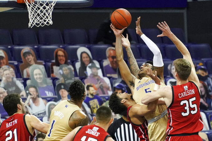 Washington forward Nate Roberts (5) puts up a shot between Utah center Branden Carlson (35) and forward Timmy Allen, third from right, during the second half of an NCAA college basketball game, Sunday, Jan. 24, 2021, in Seattle. Washington won 83-79. (AP Photo/Ted S. Warren)