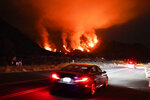 Motorists make their way along a road as the Ranch Fire burns, Thursday, Aug. 13, 2020, in Azusa, Calif. Heat wave conditions were making difficult work for fire crews battling brush fires and wildfires across Southern California. (AP Photo/Marcio Jose Sanchez)
