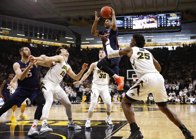Illinois guard Trent Frazier, center, drives into the lane to shoot against Iowa during the first half of an NCAA college basketball game, Sunday, Jan. 20, 2019, in Iowa City. (AP Photo/Matthew Putney)