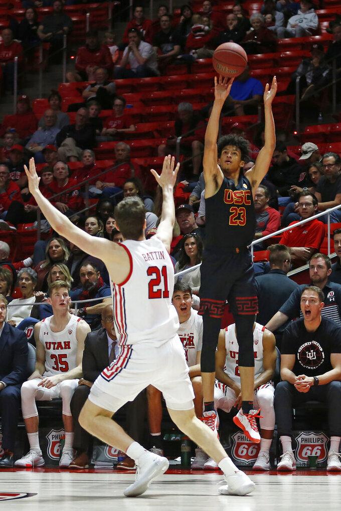 USC forward Max Agbonkpolo (23) shoots as Utah forward Riley Battin (21) defends in the first half of an NCAA college basketball game Sunday, Feb. 23, 2020, in Salt Lake City. (AP Photo/Rick Bowmer)
