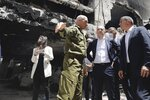 German Foreign Minister Heiko Maas, center, and Israeli Foreign Minister Gabi Ashkenazi, right, visit the site where a rocket hit in the central Israeli city of Petah Tikvah, Thursday, May 20, 2021. (AP Photo/Sebastian Scheiner)