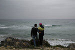 FILE - In this April 14, 2018 file photo, Ahmed Ayouby, 32, left, and Mounir Aguida, 30, who want to leave Tunisia, stand at the beach where migrants leave for Italy, in the town of Ras Jabal, Bizerte, Tunisia. The number of Tunisians migrating clandestinely to Italy has risen to levels not seen since the 2011 Arab Spring uprising. That's causing tensions in Italy's south, where more than 2,200 migrants are quarantining on ferries anchored offshore. (AP Photo/Nariman El-Mofty, File)