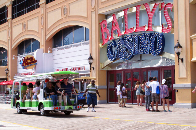 In this July 3, 2015 photo, people enter Bally's casino from the Atlantic City, N.J., Boardwalk. Caesars Entertainment and VICI Properties announced, Friday, April 24, 2020, they are selling Bally's to Rhode Island-based Twin River Worldwide Holdings for $25 million. (AP Photo/Wayne Parry)
